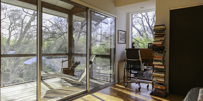 """The upstairs master bedroom is flanked by a wall of sliding glass doors on one side, leading to a screened-in porch. """"You open up the glass doors in that room, and the bedroom feels like it becomes a part of the porch, kind of that tree house idea,"""" Reeves says. """"And by having the screen on the outside, then you can have all the doors open, and no one can really see in the bedroom.""""  Photo by Jeanine Michna-Bales"""