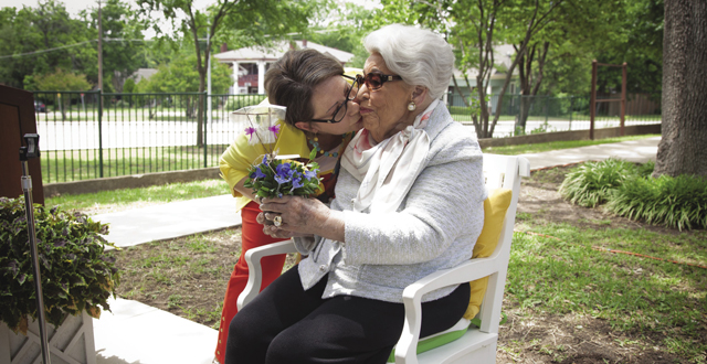 Juliette Fowler CEO Sabrina Porter gives real estate legend Ebby Halliday a kiss during the ribbon cutting ceremony for the Ebby House in May: Photo by Kim Leeson