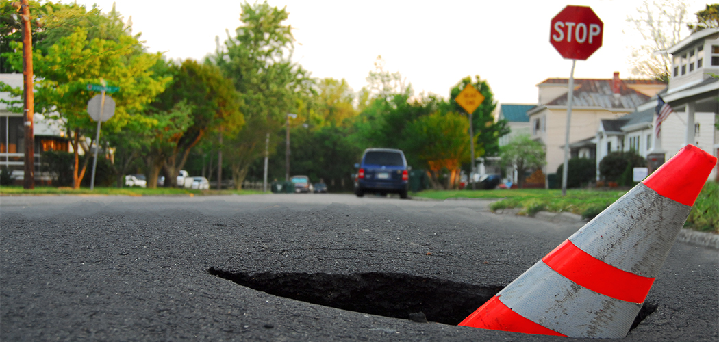 deep pothole with caution cone