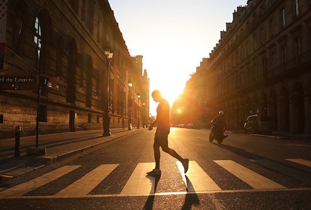 A man walks across the Rivoli street along the Louvre museum at sunset in Paris on June 8, 2015.  AFP PHOTO / LUDOVIC MARIN        (Photo credit should read LUDOVIC MARIN/AFP/Getty Images)