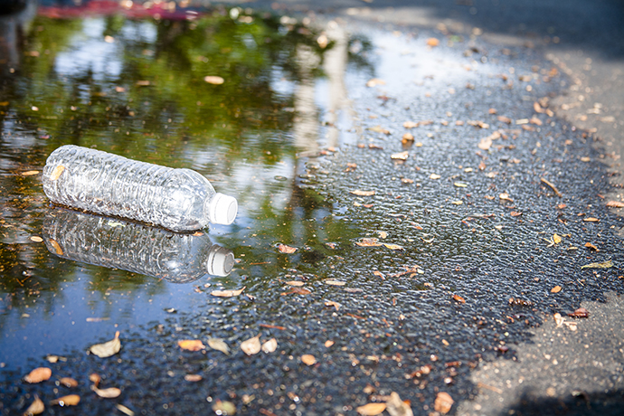 Pollution themes. An empty, plastic water bottle is discarded in rain puddle on an empty city street. No people. Recycling, pollution, environmental conservation themes.