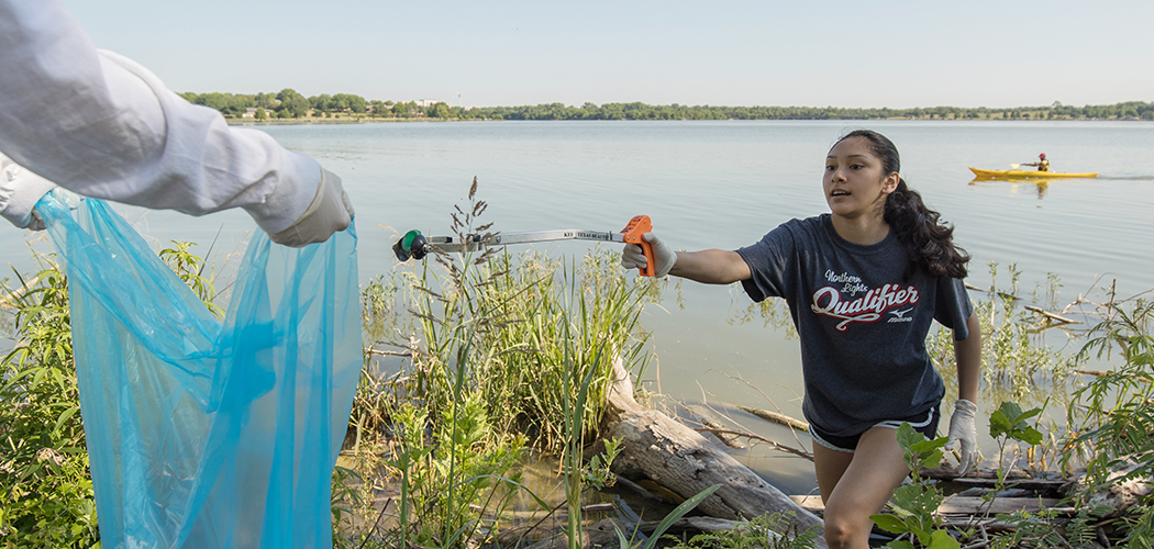 Bishop Lynch High School Freshman Alex Galicia removes trash from the west side of White Rock Lake. (Photo by Rasy Ran)
