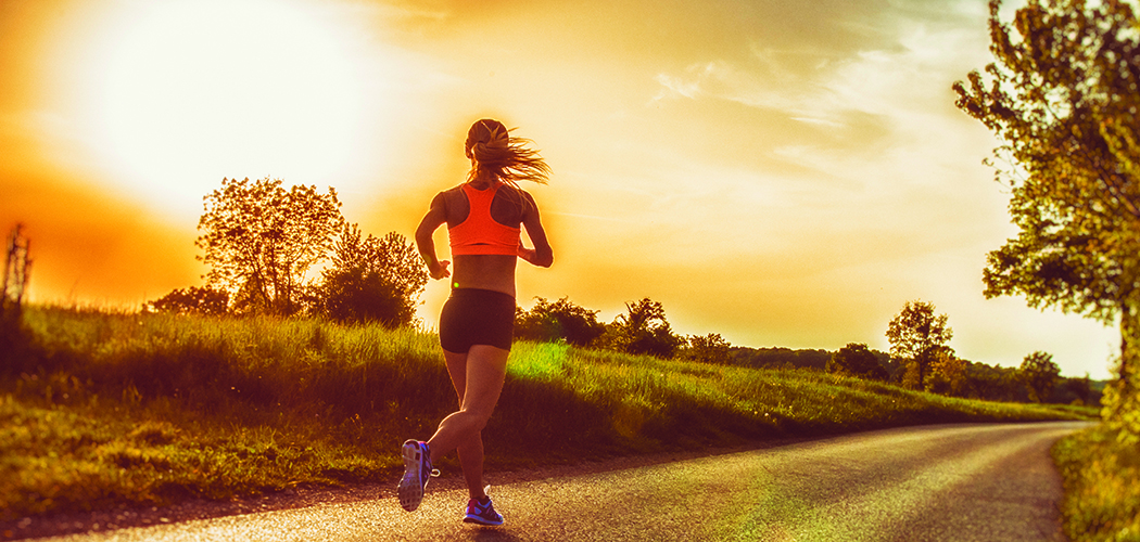 Photo of a female jogger in the countryside, with sun flare in the background.