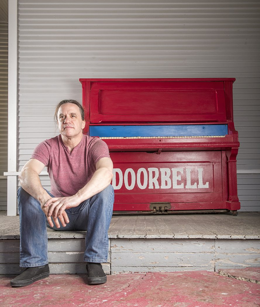 """Man in front of piano painted with """"doorbell"""" on it."""