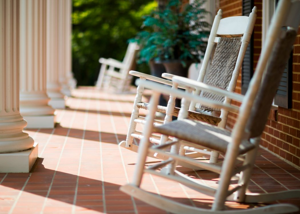 Rocking chairs sits on a brick patio with white columns.