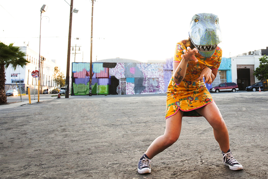 Young woman wearing a handmade dinosaur mask in an empty parking lot