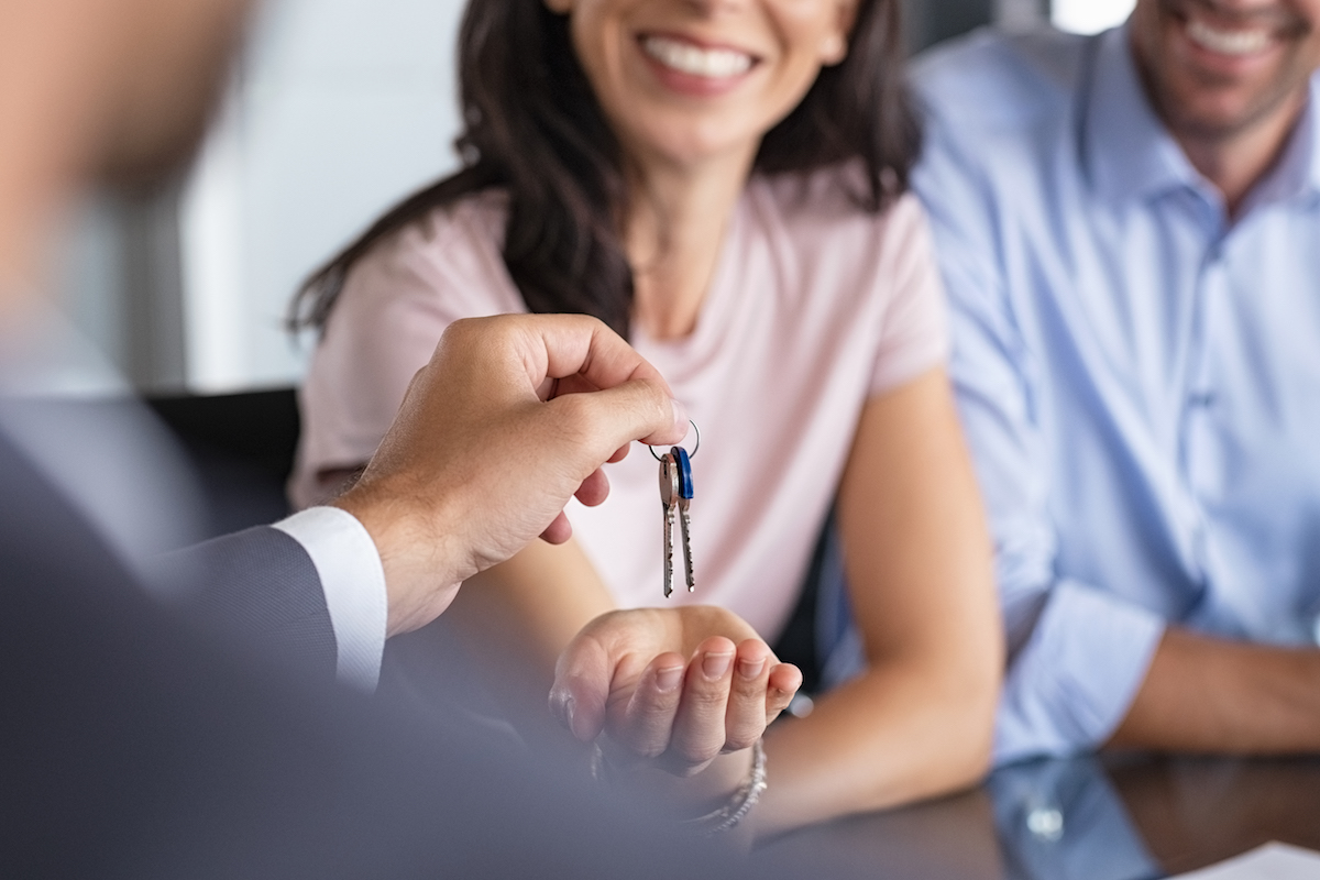 Close up of man hand giving house keys to woman. Smiling mature woman receiving new house keys from real estate agent. Man delivering keys to client for new home. Real estate agent giving keys to apartment owner.